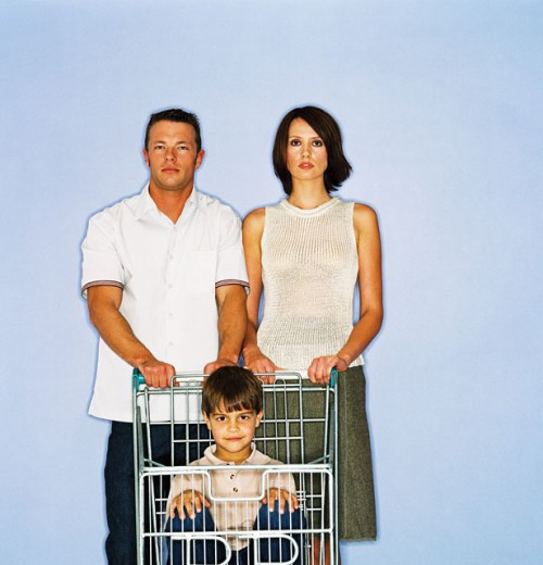 portrait of a couple pushing a shopping cart with their son in it : Stock Photo