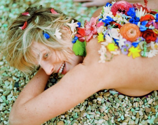 young woman lying naked on pebbles with flower petals on back : Stock Photo