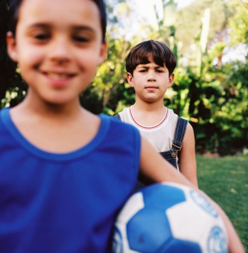 Stock Photo: 1491R-172043 close-up of a boy (8-10) standing with a football and a boy behind him