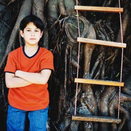 portrait of a boy (10-12) standing by a tree house ladder : Stock Photo