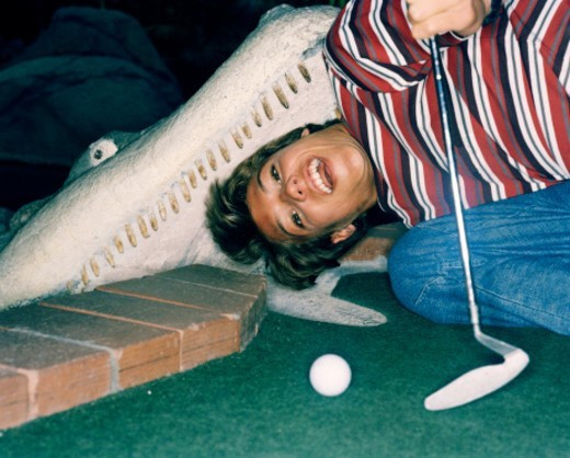 Stock Photo: 1491R-174006 a teenage boy playing miniature golf