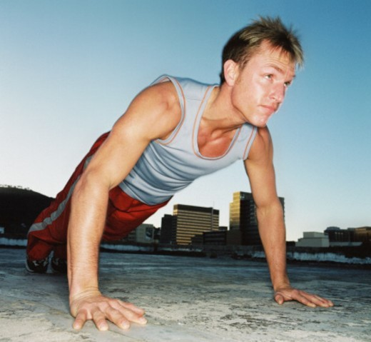 low angle view of a man doing push-ups on a roof top : Stock Photo