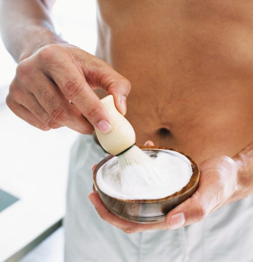 close-up of a man's hands mixing shaving cream with a brush in a bowl : Stock Photo
