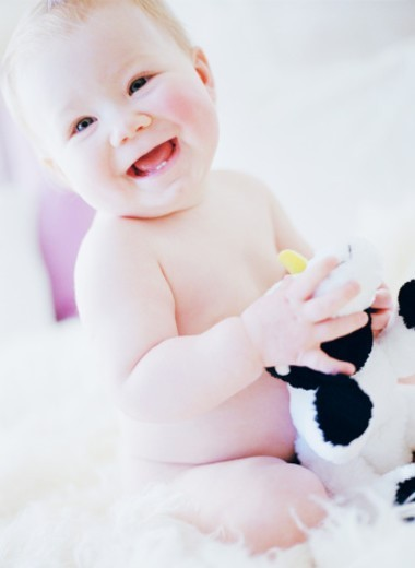 Portrait of a baby (18-21 months) smiling holding a stuffed toy : Stock Photo