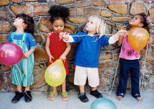 Young children (4-6) standing against a wall holding balloons : Stock Photo