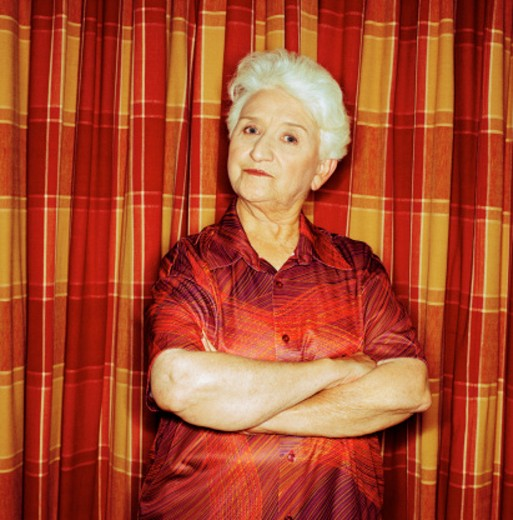 portrait of an elderly woman standing with her arms folded : Stock Photo
