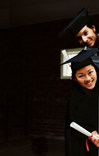 portrait of two young graduates peeping from behind a wall : Stock Photo