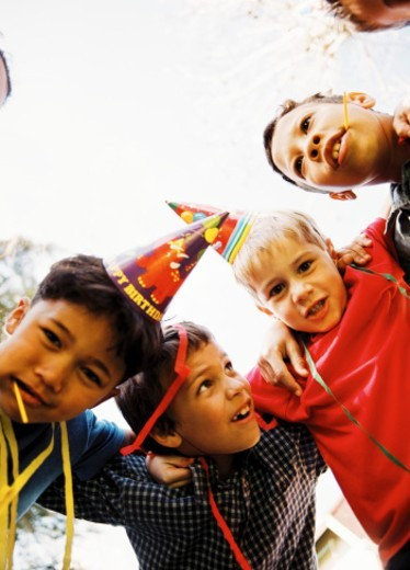 Stock Photo: 1491R-184167 low angle view of a group of boys (6-8) in a huddle at a birthday party