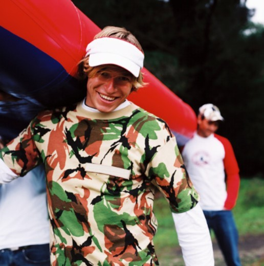 Two young men holding a raft : Stock Photo