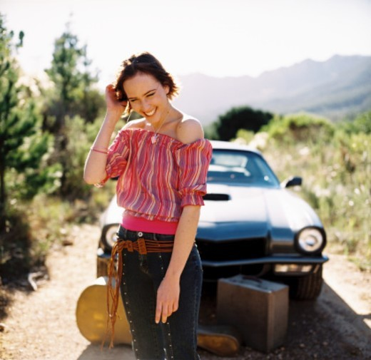 Young woman standing in front of a car laughing : Stock Photo