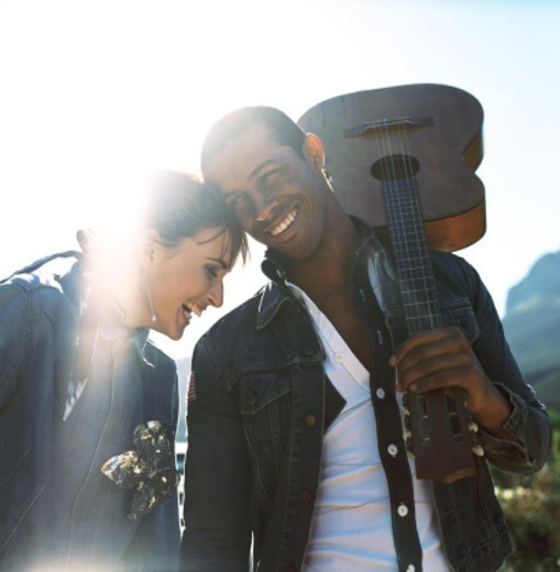Stock Photo: 1491R-185060 Young couple holding a guitar smiling outdoors