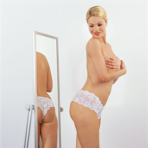 Stock Photo: 1491R-222051 side view of a woman looking at her buttocks in a mirror