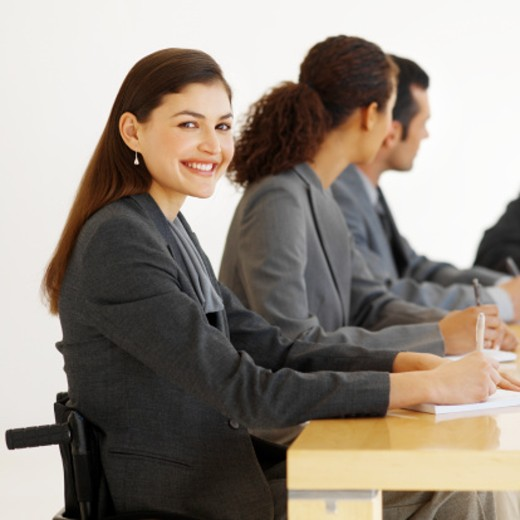 Stock Photo: 1491R-223058 Business executives having a meeting around a table and one of them sitting in a wheelchair
