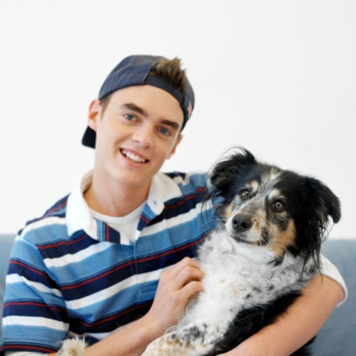 Stock Photo: 1491R-229115 portrait of a boy (16-18) sitting on a chair holding a shepherd dog