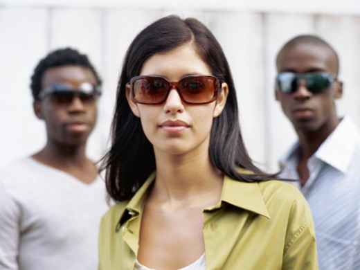 portrait of three young people standing together and wearing sunglasses : Stock Photo