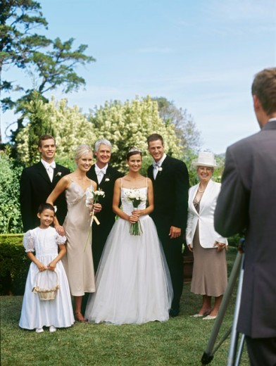 Stock Photo: 1491R-239013 bride and groom standing with their parents and guests posing in front of a camera