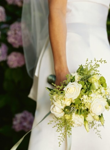 Stock Photo: 1491R-239073 mid section view of a bride holding a bouquet of flowers