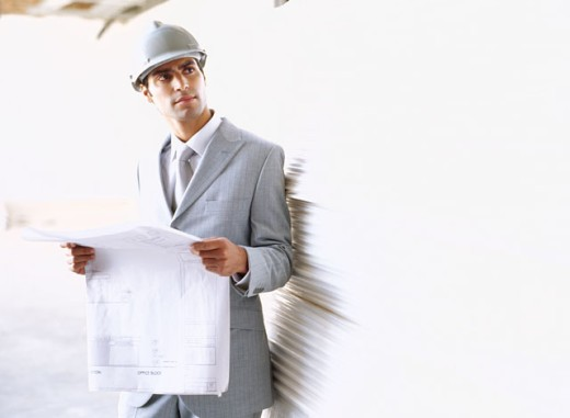 architect holding blueprints at a construction site : Stock Photo