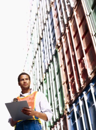 low angle view of a foreman holding a clipboard, standing at a commercial dock : Stock Photo