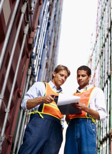 low angle view of two foremen looking at a clipboard, standing at a commercial dock : Stock Photo