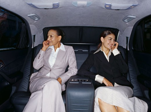 two businesswomen talking on mobile phones in a car : Stock Photo