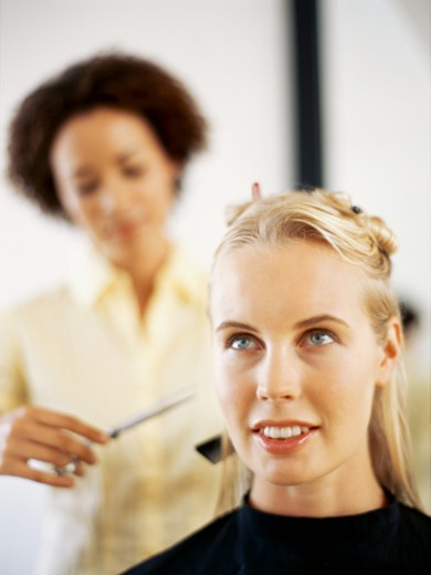 Stock Photo: 1491R-249066 hairdresser cutting a young woman's hair