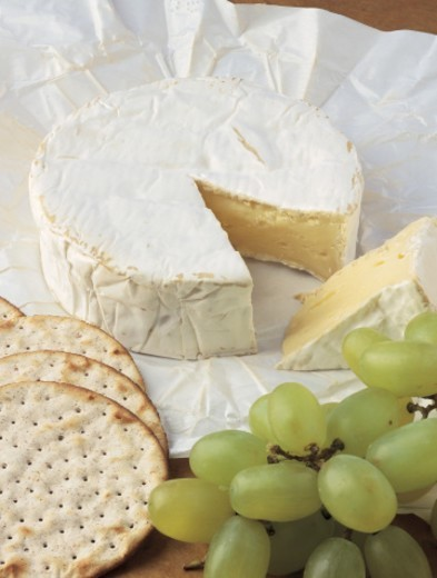 close-up of a block of cheese with cracker and grapes : Stock Photo