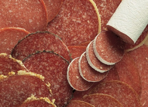 high angle view of a salami roll on top of sliced salami : Stock Photo