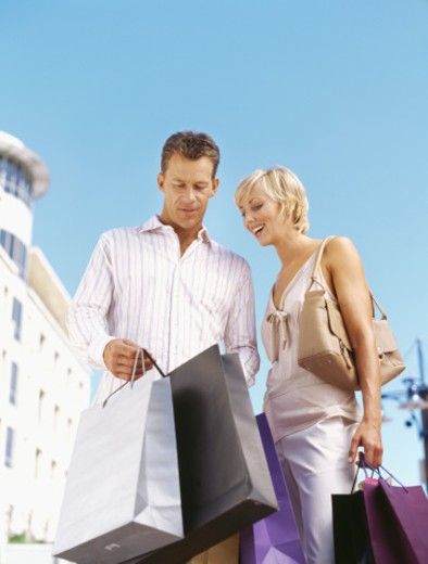 Stock Photo: 1491R-251010 low angle view of a mid adult couple holding shopping bags