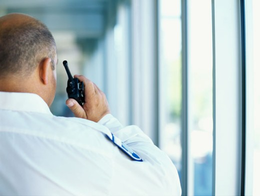 rear view of a security guard talking on a walkie talkie in an office : Stock Photo