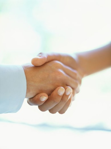 close-up of a businessman and a businesswoman shaking hands : Stock Photo