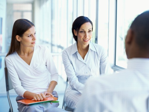 two businesswomen and a businessman discussing in an office : Stock Photo
