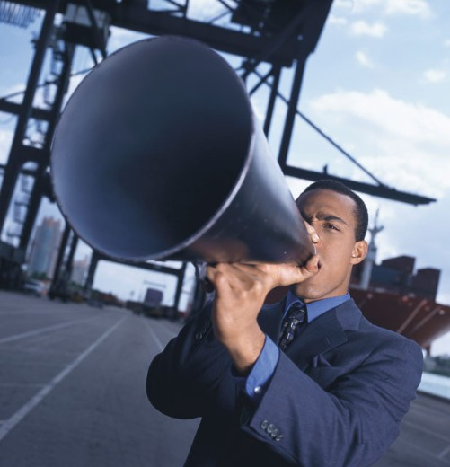 close-up of a businessman speaking through a loudspeaker : Stock Photo