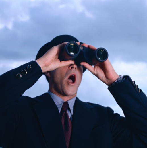 Stock Photo: 1491R-87099 close-up of a businessman in a hat looking through binoculars with mouth open