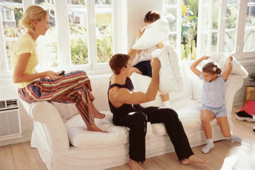 view of a father and mother having a pillow fight with their children (4-8) : Stock Photo