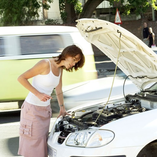 woman checking an oil dipstick : Stock Photo