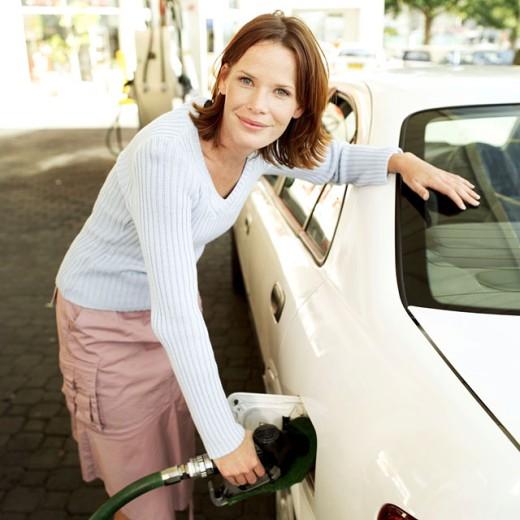 portrait of a woman filing a car with petrol : Stock Photo