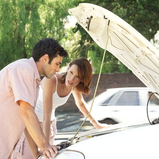 Stock Photo: 1491R-975506 man and woman leaning over a car engine