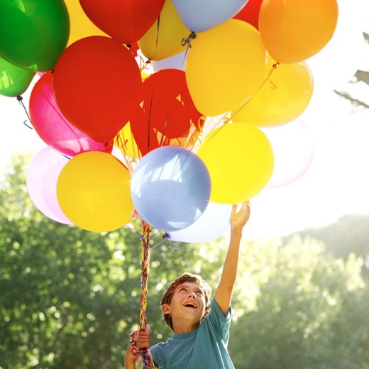 low angle view of a boy holding balloons : Stock Photo