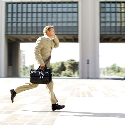 businessman talking on a mobile phone while running : Stock Photo