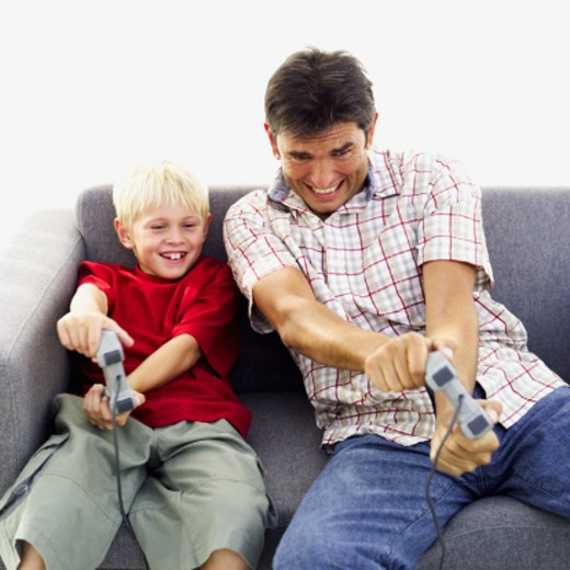 father and son(6-7) playing a videogame : Stock Photo