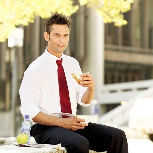 portrait of a businessman sitting eating a sandwich : Stock Photo
