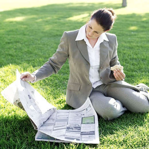 businesswoman sitting in a lawn eating a sandwich and reading a newspaper : Stock Photo