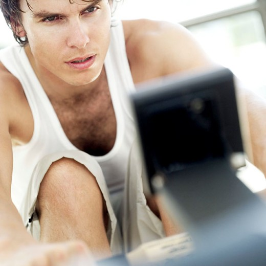 portrait of a young man on an exercise machine : Stock Photo