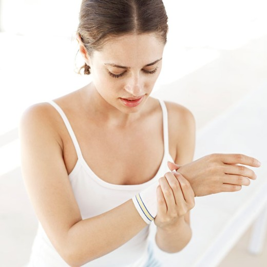close-up of a woman putting on a wristband : Stock Photo