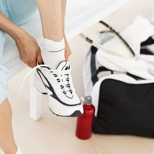 Woman putting on gym shoes : Stock Photo