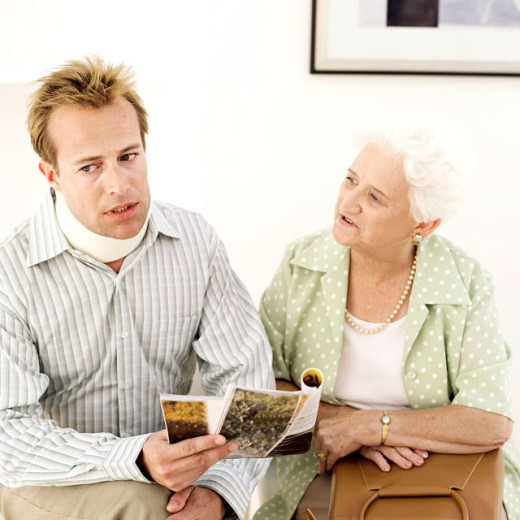 man wearing neck brace sitting with elderly woman in a waiting room : Stock Photo