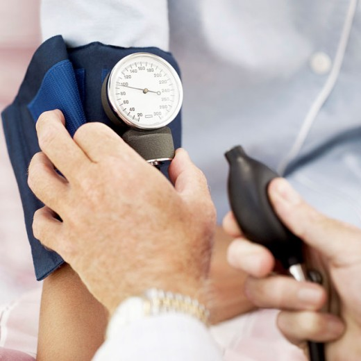 Close-up of a pair of human hands checking the blood pressure of a patient : Stock Photo