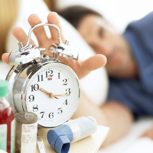 close-up of an alarm clock being put off by a sleeping man : Stock Photo