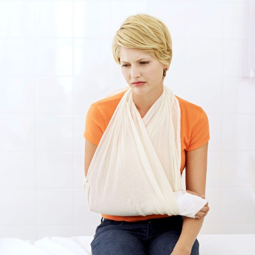woman sitting with her arm in a sling : Stock Photo